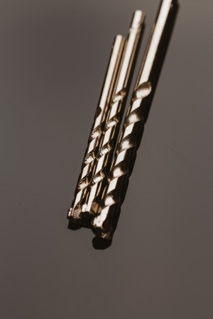 Drill bits of different sizes over dark background.
