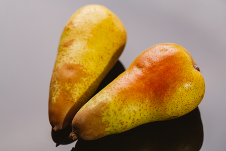 several fresh pear on a dark background.