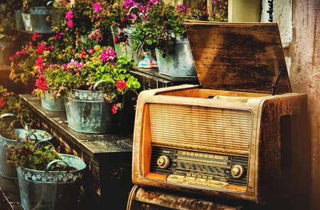 altes Radio auf dem Hintergrund der Töpfe von Blumen