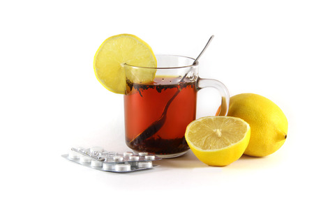 hot drink with a lemon with drugs for colds and flu, isolated on white background Stock Photo