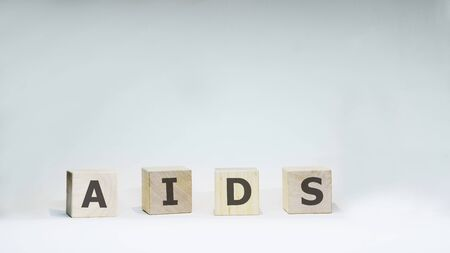 Word AIDS with wooden letters on white background. 스톡 콘텐츠