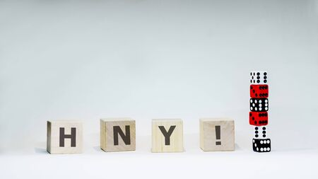 Word HNY with wooden letters with six dices on white background.