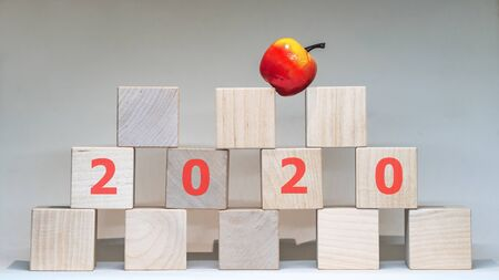 Word 2020 with wooden letters with apple on top on a white background. 스톡 콘텐츠