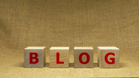 Wooden cubes with word BLOG on sackloth background. Business concept