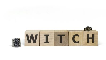 Wooden cubes with word WITCH and two mystical rings on white background. Mystical concept. Zdjęcie Seryjne