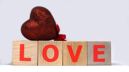 Wooden cubes with word LOVE and red heart on white background. Valentines concept