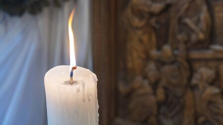 Burning candle in the church on a blurred background. Christmas and Easter concepts.