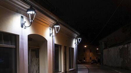 Old street at night. Street llamps on the wall building. Standard-Bild - 140245975