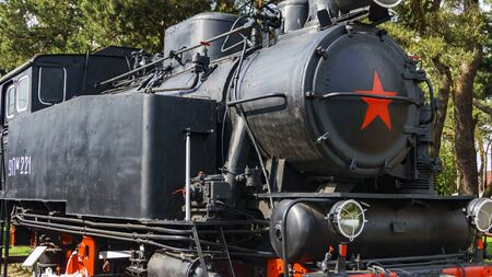 Close-up view of old classic black steam locomotive with red decoration.