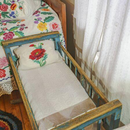 Traditional slavic cradle with ornament towel in the room. Archivio Fotografico