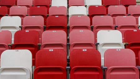 Empty red and white plastic seats with numbers at the stadium. Sport concept. Stock Photo