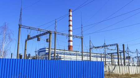 Thermal power station, electric wires and poles on classic blue sky background. Green power and ecological problem.