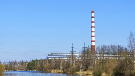 Chimney in thermal electric generator industry plant on classic blue sky background. Green power and ecological problem. 免版税图像