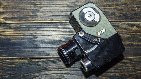 Vintage old movie camera on the wooden table. Space for text.
