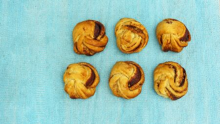 Top view of some sweet cinnamon buns on the blurred turquoise background. Danish pastry. Sweet pastry for breakfast or snack. Space for text.