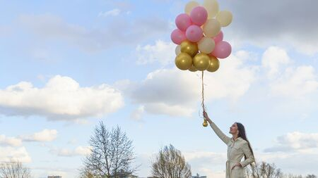 Happy woman with balloons on the background of the classic blue sky. Celebration on nature outdoors. Reklamní fotografie