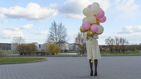 Happy woman with balloons on the background of the nature. Celebration on nature outdoors. Reklamní fotografie