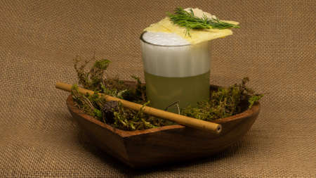 Boozy alcoholic moonshine cocktail with moss and drink straw. Alcohol, schnapps. Bar concept.