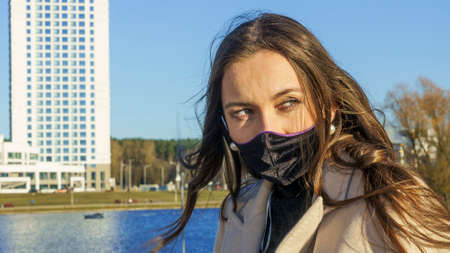 Young woman in protective mask on the street in the city with air pollution or pandemic situation. Coronavirus concept. Stok Fotoğraf
