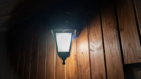Glowing street lamp on the background of a wooden wall at night. Light permeates the darkness. Street lighting. Creating a cozy. Space for text.