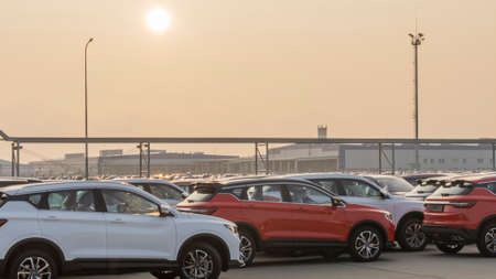 New cars lined up parking outside factory on car factory background. Standard-Bild