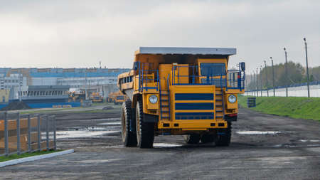 Heavy mining dump trucks are at the factory. Giant mining truck after being from the conveyor is tested at the factory test site. Heavy-duty truck manufacture by the heavy vehicle plant.