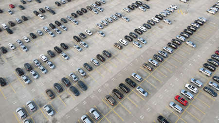 Aerial view of new cars lined up parking outside factory on car factory background.