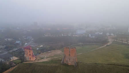 Aerial view of ruins of Tower Shchitovka and Mindovg Castle in Novogrudok, Belarus. Foggy landscape.