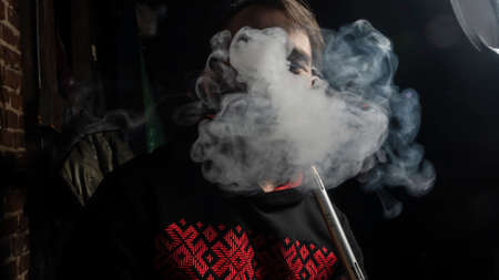 Brutal man with large beard and fashionable haircut smokes an electronic cigarette or hookah on dark background.