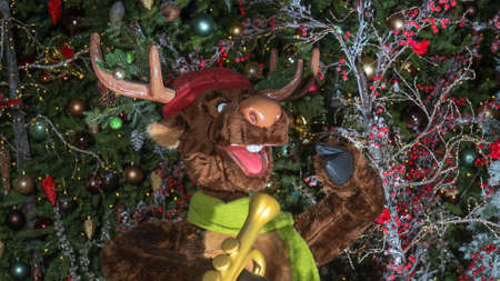 Christmas and New Year Decoration. Toy in the form of moose on christmas tree background.