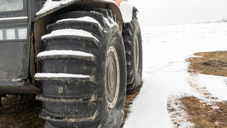 Large wheels with the tread of an all-terrain vehicle in the winter. Powerful off-road transporter. Engine, cross.
