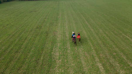 Aerial view of group of fox hunters on the horses in the autumn field. Equestrian riding sport in a countryside. Traditional hunting concept.