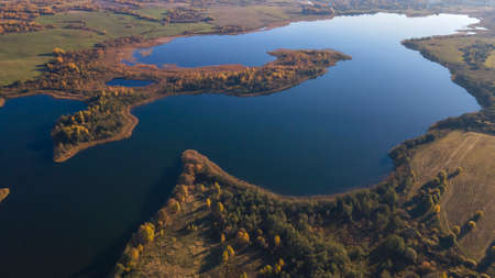 Autumn forest and lake. View from the top. Aerial Photo of an Island in Lake on Sunny Autumn Day. Nature concept.