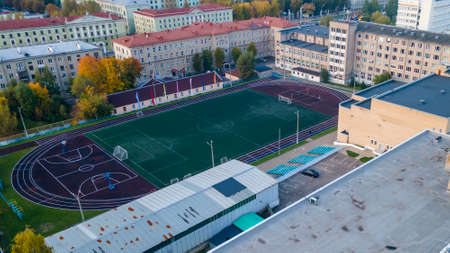 Aerial view of all weather track and field stadium around by residential buildings inthe city. Top view of the football stadium. Foto de archivo
