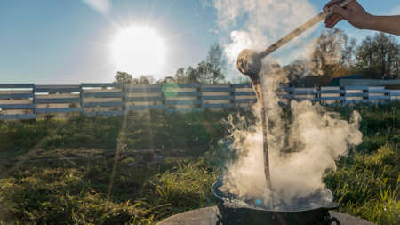 Camping stove and steam coming out of the bowl in a sunny day with blue sky during camping adventure. Outdoor cooking, tourism, traveling, camping concept.
