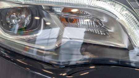 Close-up element of reflector of new car headlight headlight. Car background with soft focus. Headlight lamp of new cars. Close up detail on one of the LED headlights modern black car.