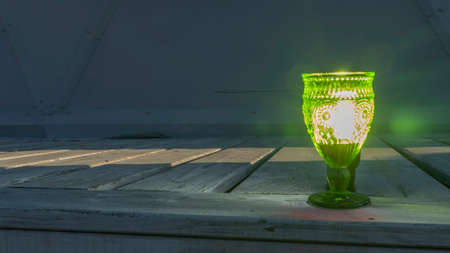 Illuminated empty glasses of green glass on a stem on a wooden background. Close-up view. Space for text.