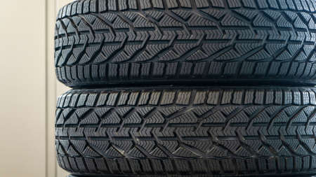 Stack of new winter tires. Group of automotive tires for snow road. Selective focus. Sale tires in shop. Safety concept. Foto de archivo