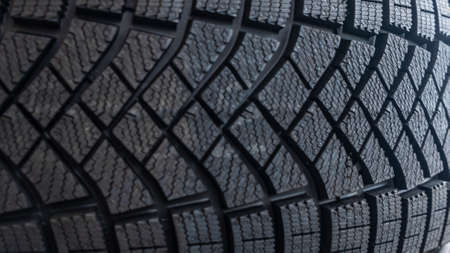 Close-up view of the winter tread of a new tire in shop. Automobile tire for snow road. Selective focus. Sale tires in shop. Safety concept.