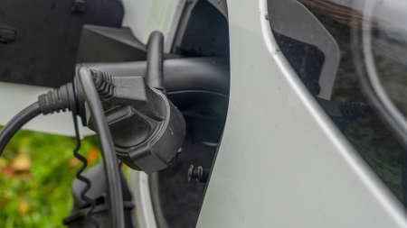 Close-up view of power supply plugged into an electric car being charged. Electric car charging. Back side of the car loading energy.