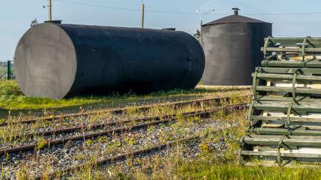 A metal fuel tank in an antique railway yard. Old black Fuel Tank on the village railroad station. Industry concept. Foto de archivo