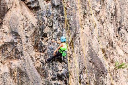 rappel: Basalt Challenge Of Tungurahua, Ambitious Girl Climbing A Rock Wall Stock Photo