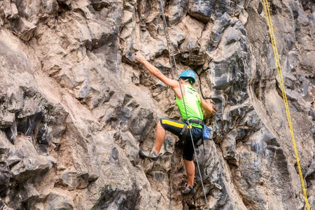 mountain climbing: Basalt Challenge Of Tungurahua, Man Climbing Vertical Rock Wall