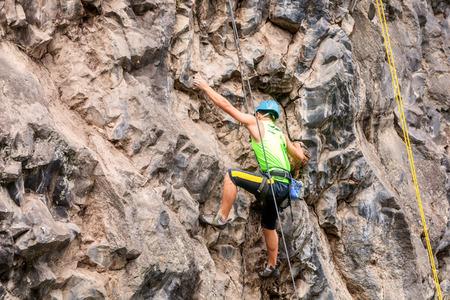 escalando: Basalto desafío de Tungurahua, hombre que sube vertical pared de la roca Foto de archivo