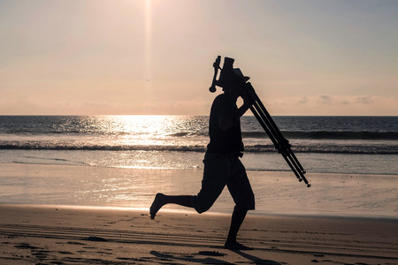 professional man: Silhouette Of Professional Man Photographer Running With His Tripod On The Galapagos Beach, South America