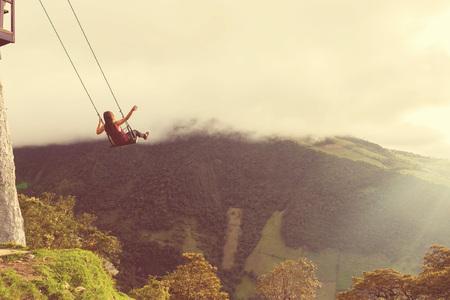 columpio: Silueta de una mujer joven feliz en un columpio, balanceo Sobre las montañas de los Andes, de árbol, Ecuador, del estilo de la vendimia
