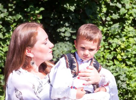 campesino: Joven Madre Campesina De Rumania tratando de persuadir a su hijo a Pose Foto de archivo