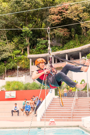 Banos, Ecuador - 23 May 2015: Young Guide Performs In Public A Rope Climbing Exercise In Banos On May 23, 2015