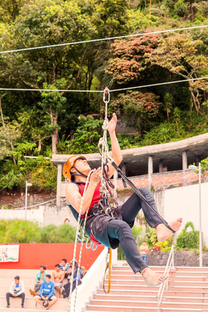 Banos, Ecuador - 23 May 2015: Young Hispanic Guide Performs In Public A Climbing Rope Exercise In Banos On May 23, 2015