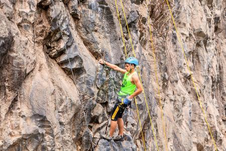 lead rope: Banos, Ecuador - 30 November 2014: Basalt Challenge Of Tungurahua, Young Hispanic Man Climbing Vertical Rock Wall In Banos On November 30, 2014 Editorial